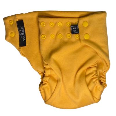 En gul tygblöja med knäppfunktion delvis öppnad.